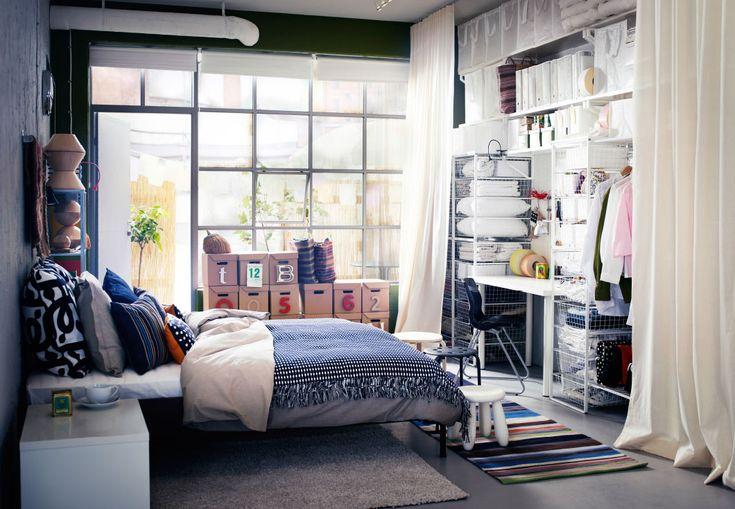 衣類や靴の収納とデスクが一体になった収納ソリューションを壁際に設置したモダンなベッドルーム。全面ガラス窓の前に枕をたくさん並べた大きなベッドを置いて。
