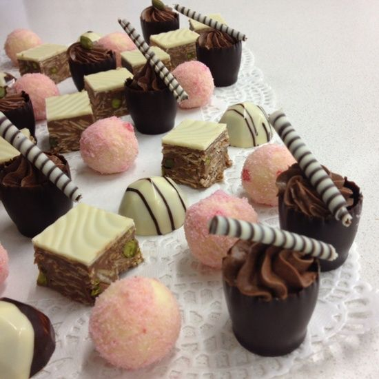 Mini chocolate cups topped with a chocolate swirl, pink truffles and chocolate squares