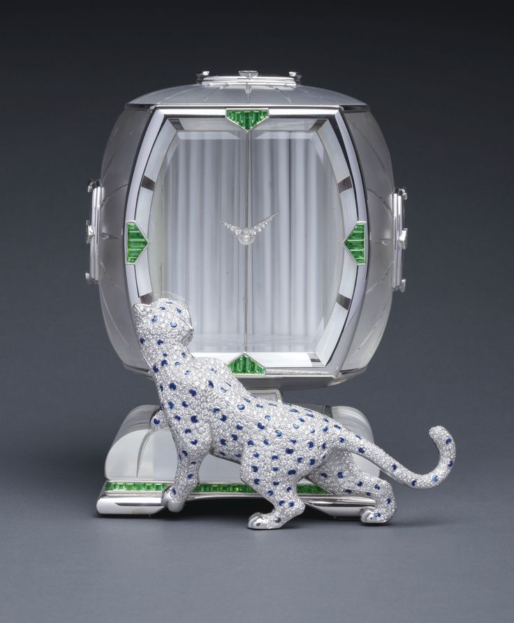 "Asprey ""The Art-Deco Inspired Panther Mystery Clock"" A SUPERB WHITE GOLD, DIAMOND, SAPPHIRE, GREEN TOURMALINE, WHITE AND BLACK MOTHER-OF-PEARL AND ROCK CRYSTAL PANTHER MYSTERY CLOCK CIRCA 1985"