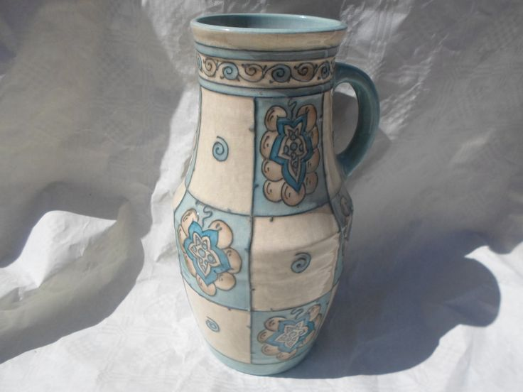 A 1940s HJ Wood Bursleyware tall vase with single handle, designed by Charlotte Rhead in the TL31 pattern, having a tube-lined decoration of stylized star shapes and fruits in panels in shades of blue, on an ivory ground, printed and tubed marks verso to include the 'Arabesque by Charlotte Rhead' stamp, 28cm tall