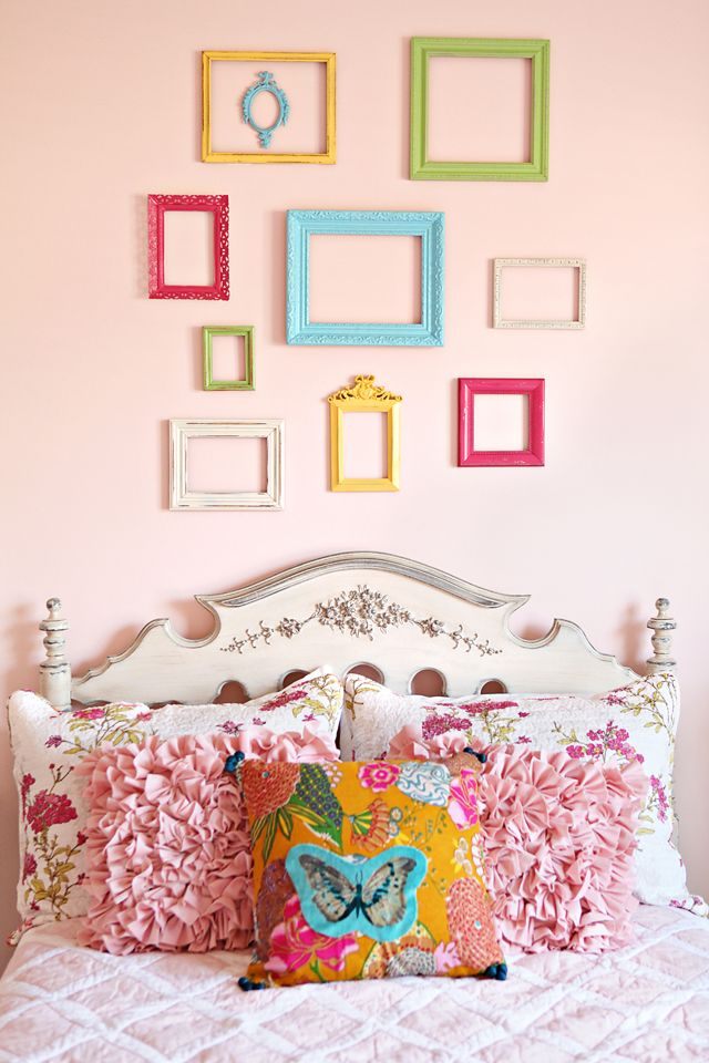 Picture frames in bold colors on soft light pink wall
