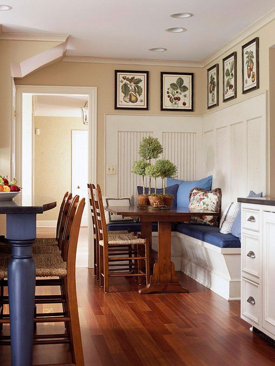 To unite your kitchen with an adjacent dining nook, use similar decor elements in both spaces, but also consider treatments to make each space unique. Here, the blue from the island is repeated on the cushions on the breakfast nook bench, and the dining chairs are the same style as the barstools. The beaded board of this dining area runs up the wall, distinguishing the area from the rest of the kitchen.