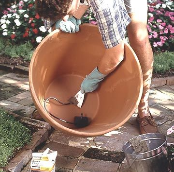 Set a submersible pump in the bottom of the container. Using a pot that is at least 24 inches in diameter makes a splash and requires less water refilling than a smaller pot. Pull the pump electrical cord through the drainage hole of the pot.