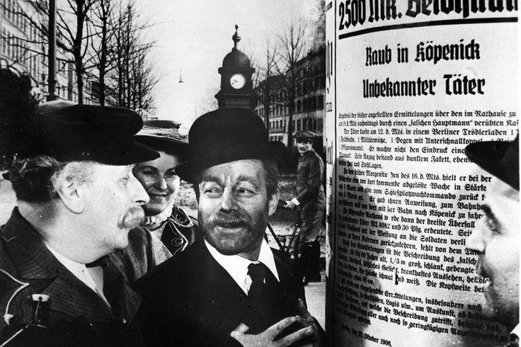 """Selbst die Nachbarn ahnten nichts: Wilhelm Voigt tarnte sich so geschickt, dass ihn zunächst niemand mit der Tat in Verbindung brachte. In seiner Autobiografie ist zu lesen, wie er sich die Steckbriefe an den Litfaßsäulen ansah und sie den Umstehenden sogar laut vorlas. Hier spielt Heinz Rühmann diese Szene im Film von Helmut Käutner. Verfilmt wurde die """"Köpenickiade"""" mehrfach, 1997 auch mit Harald Juhnke."""