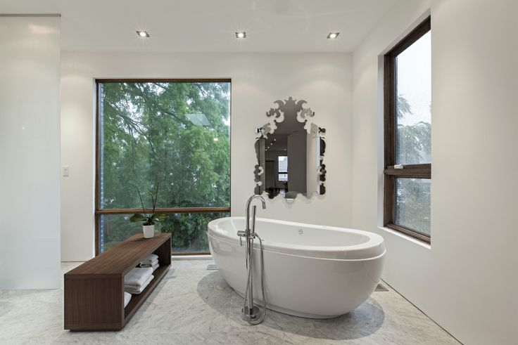 rzlbd > Totem House > Beautiful marble tiles separate the shower and the bathtub area from the rest of the hardwood floor. The freestanding bathtub installed in the corner of the room has a peaceful corner view to the courtyard.