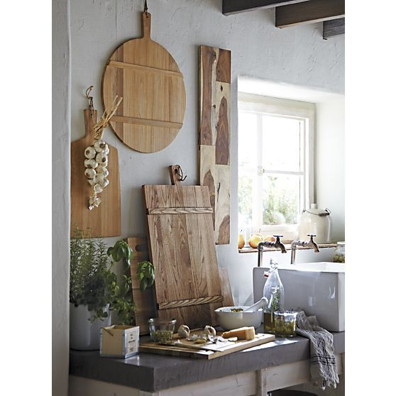 Wood serving boards hanging on wall as decoration - in dining room above bookcase? various shapes, angles, and wood grains. FSC Teak Paddle Board  | Crate and Barrel - $39.99, J.K. Adams Heritage Serving Board (C&B $99), Palisades Cheeseboard (C&B, $69)