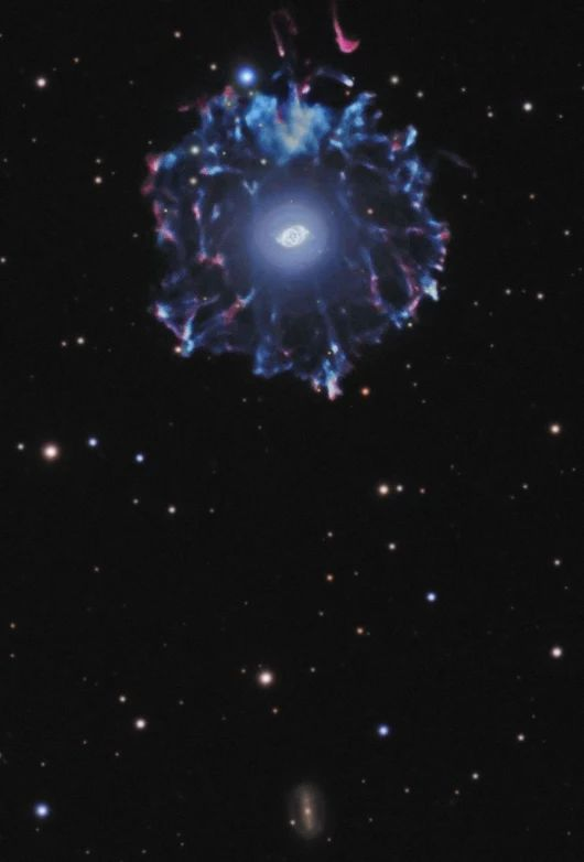 The Cat's Eye Nebula (NGC 6543) is one of the most well-known planetary nebulae. In this stunning wide-angle view, you can see the most familiar contours of the brightest central region of the nebula. The composition combines many short and long exposures which also reveal an extremely faint exterior halo.