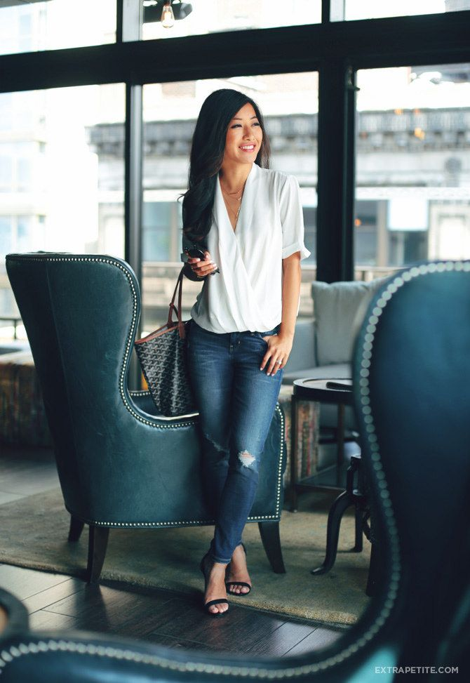 Casual outfit staples: white crossover drape tee, ripped skinny jeans, goyard bag, strappy heels
