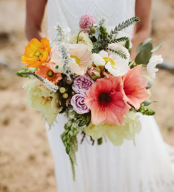 This colorful bouquet is all kinds of wonderful. Brimming with poppies, lavender roses, bright hibiscus flowers and a touch of greenery, it sure pops against the desert setting.