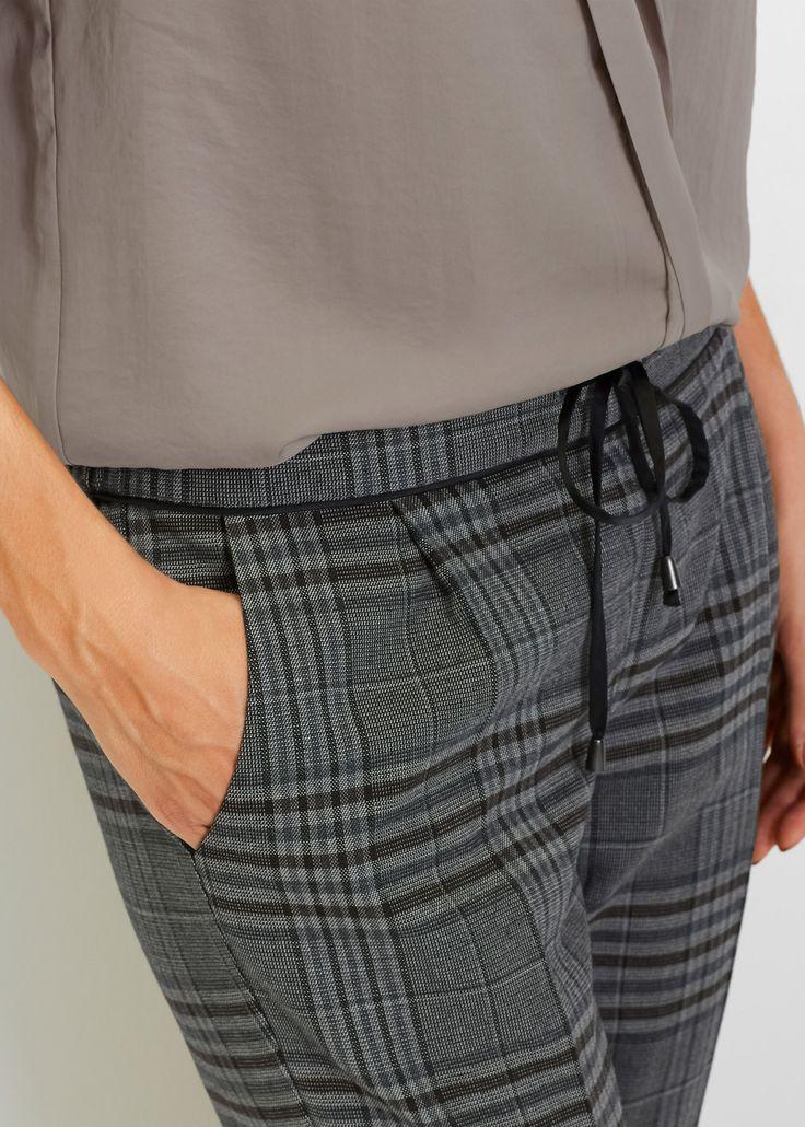Diese elegante 7/8-Glencheque-Hose begleitet Damen stilvoll durch den Alltag. Die bequem geschnittene Hose in fließender Stoffqualität überzeugt mit seitlichen Eingrifftaschen, zwei Gesäßtaschen, dem Tunnelzug am Bündchen und dem Aufschlag am Bein.