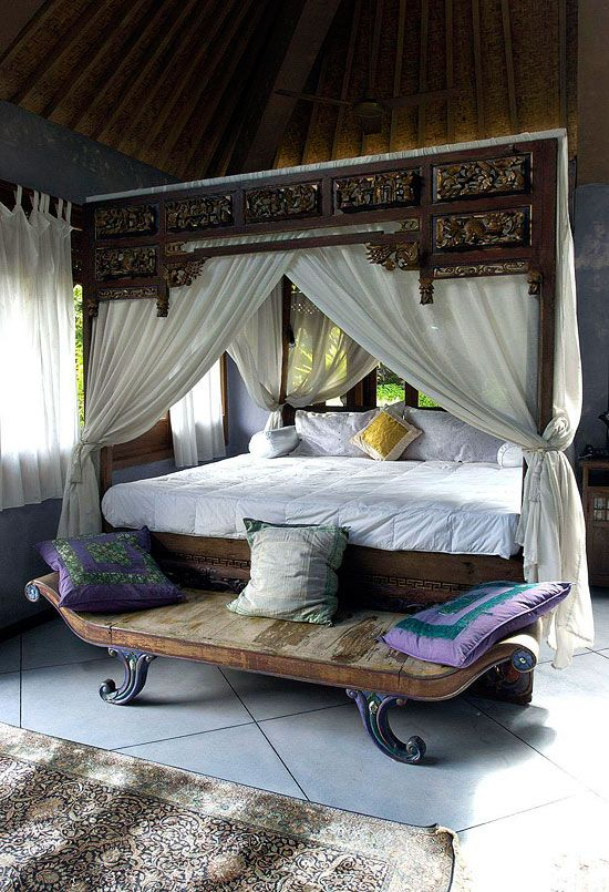 A 19th-century opium bed airily dressed in a simple white canopy with curtains tied back to the bedposts establishes the South Pacific style of jewelry designer Carolyn Tyler. Lavender terrazzo floors splash the pastel jewel tone underfoot. The oversize tiles also offer a starkly simple counterpoint to the intricate carving of the bed.