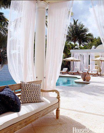 Gauzy curtains give the pool area a breezy tropical feel.   - HouseBeautiful.com
