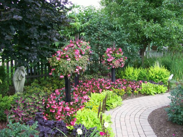 Our Own Garden Oasis, Colorful use of containers and  creative use of space creating a front and backyard garden oasis, Focal impact in a small area with baskets on columns under-planted with BIG Begonias and Sweet Potato Vine., Gardens Design