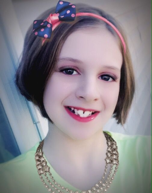 In this picture, I am wearing Pink in Many eyeshadow, Bold Black mascara, Kitty Kat eyeliner, and Perfect Pink lipstick. I added a little more by putting on a golden necklace with stars all around and a pink headband with blue bow and pink polka dots.