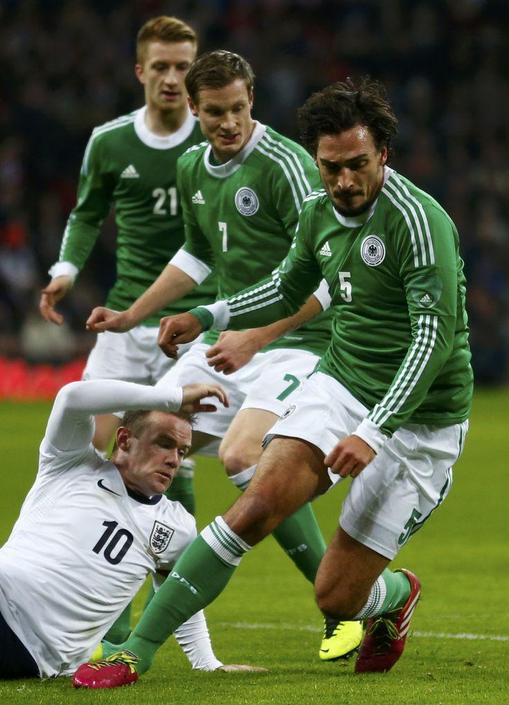 Too many Germans! - Wayne Rooney falls at three German defenders' feet.