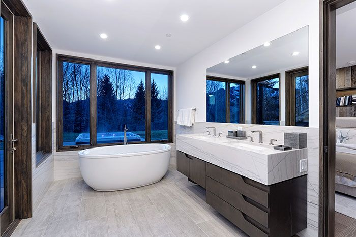 This contemporary Aspen home makes a grand statement with oak finishes and cloud-like interiors. | Colorado home design and architecture, contemporary mountain home design, white interior design, bathroom design, dream bathroom, luxury bath