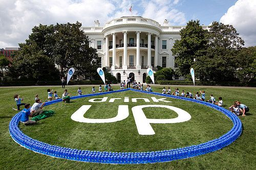 First Lady Michelle Obama and children from local YMCA organizations and the Arlington County Department of Parks and Recreation show off the Drink Up logo during an event on the South Lawn of the White House, July 22, 2014. (Official White House Photo by Chuck Kennedy)