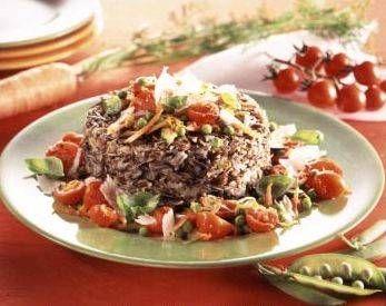 Il riso venere diventa protagonista di un primo piatto vegetariano con carote, piselli, zucchine e pomodorini, che può diventare anche un piatto unico.