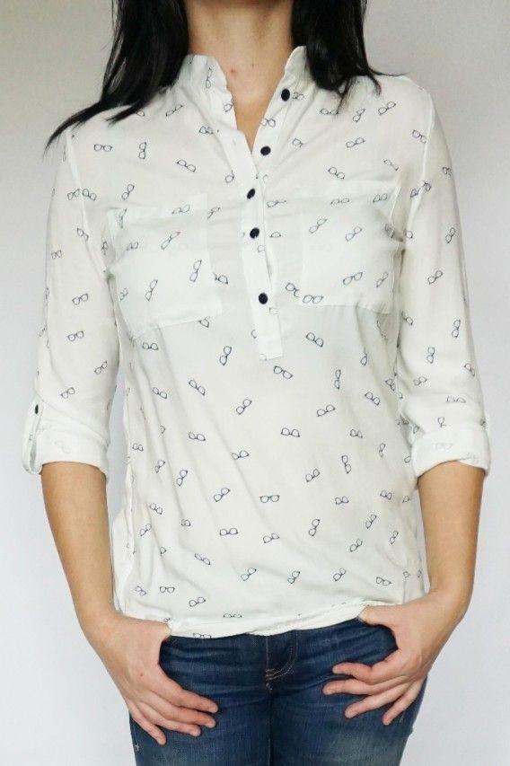 Koszulowa bluzeczka ze stójką zapinana od góry na pięć guzików. Zakończona na dole gumką. Kolor nie jest czysto biały (delikatnie wpada w zieleń bardzo słabo widoczną) widać to tylko przy przyłożeniu do bieli.