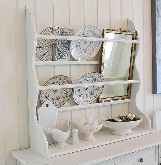Hvit tallerkenhylle med hvitt og blåhvitt porselen, og et lekkert speil.