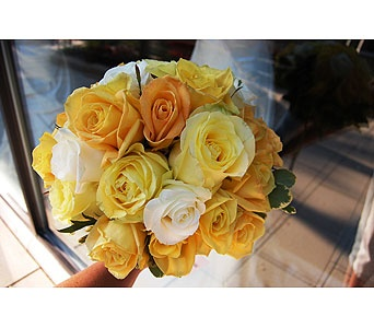 Hand tied bouquet of roses in two shades of yellow and cream.
