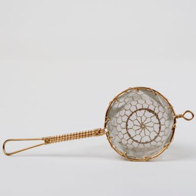 """Yoshio Tsujii specializes in wire netting craft, a skill he learned from his father. This lovely handmade tea strainer is constructed of copper wire with stainless steel mesh, functioning as both a beautiful object and a practical utensil. The artist works and lives in Kyoto, a city well known for its role in the preservation of traditional Japanese craft, culture and aesthetics."""