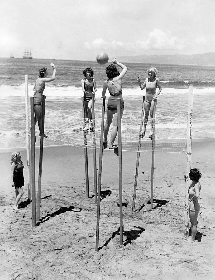 Four young women playing volleyball on stilts at the beach in Venice, California, 1934.