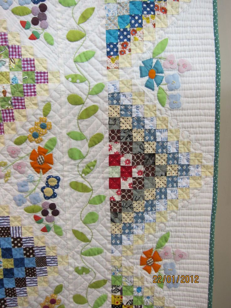 Detail of border of Many Trips Around the World Applique vine, half Trip Around the World blocks, applique flowers in a nice mix.