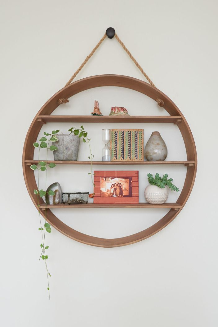 The circular wall shelf from World Market is decorated with little tiny plants and knickknacks.