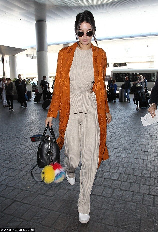 Stylish traveler: Kendall Jenner livened up her beige jumpsuit with a rust-colored duster coat while arriving at LAX ahead of a flight on Tuesday