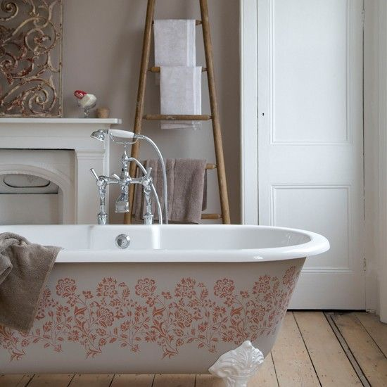 Serene country bathroom  This roll-top bath has been given a new lease of life using a stencil with a pretty rose damask pattern in a terracotta shade. Accessorising with linen damask hand towels highlights the pattern further.