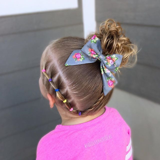 A line of elastics down the left side of the hairline, a rope twist, and a high messy side bun! Toddler hair ideas