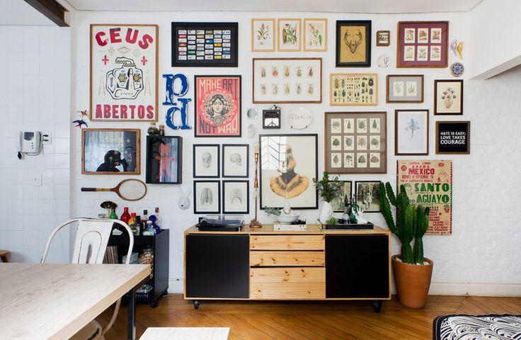 A sala dessa casinha dos anos 30 tem parede de tijolos brancos com galeria de quadros e objetos das moradoras.