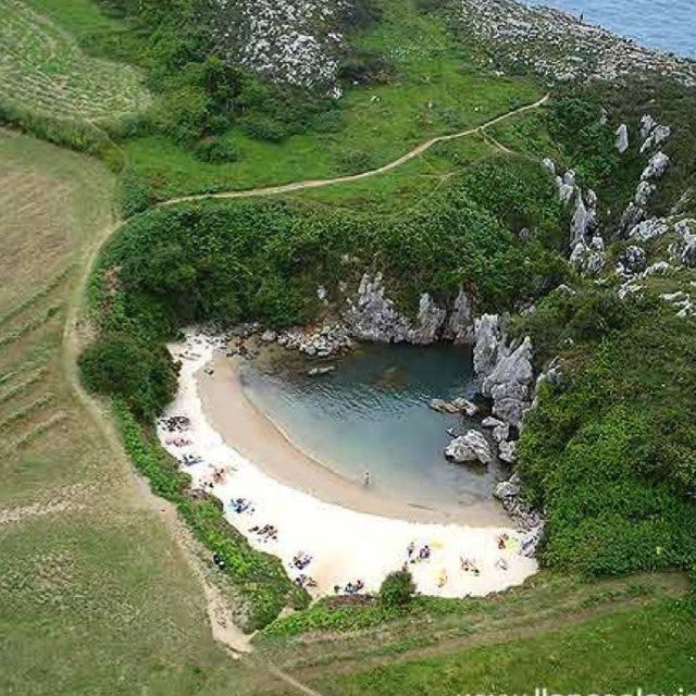 Gulpiyuri Beach, located near the town of Llanes on the northern coast of Spain, is a small charming beach in the middle of a meadow...complete with tides and waves!
