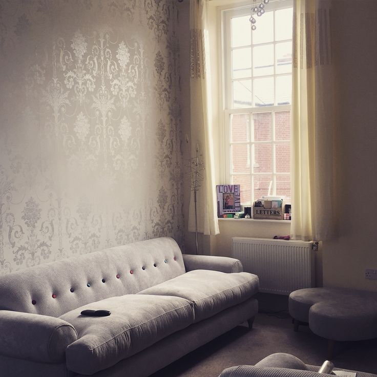 Laura Ashley Josette Wallpaper in Silver Glitter. Furniture is DFS Saturn in Silver with Multicoloured button detail to back.