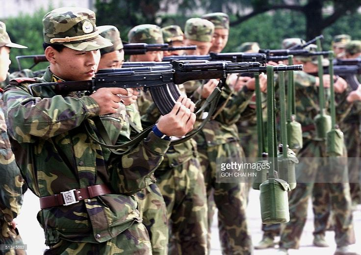 Chinese People's Liberation Army (PLA) soldiers train to hold their rifles steady by hanging water bottles on the barrels during a workout near their barracks in Beijing 23 May 1999. Forced onto the back foot by reforms and shorn of its business empire, the PLA is reasserting itself as it revels in the fury unleashed by the NATO bombing of China's embassy in Belgrade, with calls for the three-million-strong army to have more funds for modernisation to counter perceived threats. (ELECTRONIC…