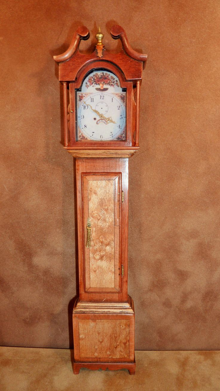 Keith Bougourd Pagoda Longcase = This is a beautifully done longcase working clock on Eastern Standard Time. It has a pagoda top face which is exceptionally colorful and topped with one finial. It is handcrafted from pear wood and English walnut. $397. Z