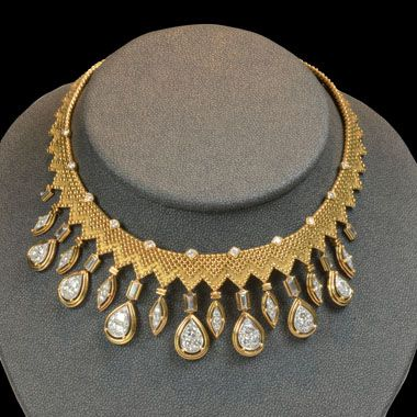 Striking 18ct yellow gold necklace designed as a woven flexible collar with diamond point accents and matted zig-zag border, the central section suspending a series of alternating pave-set brilliant-cut diamond navette and pear shape drops, Cartier, London. Circa 1970