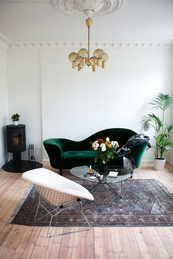 vintage green velvet sofa with a stunning golden globe chandelier. Narrow wood floor with an off white finish.