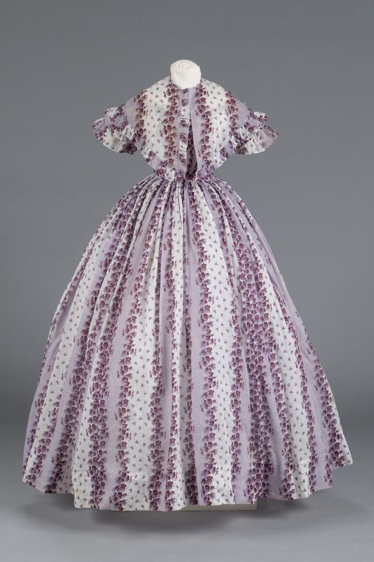 1855-1860 Matching dress and pelerine. White cotton dress with printed design of purple horizontal stripes alternating with vines of ivy also in purple. The dress is high waisted with a full length skirt, off-the-shoulder neckline, gathered bodice, and short sleeves. The sleeves have double ruffle at end. Pelerine in matching fabric.
