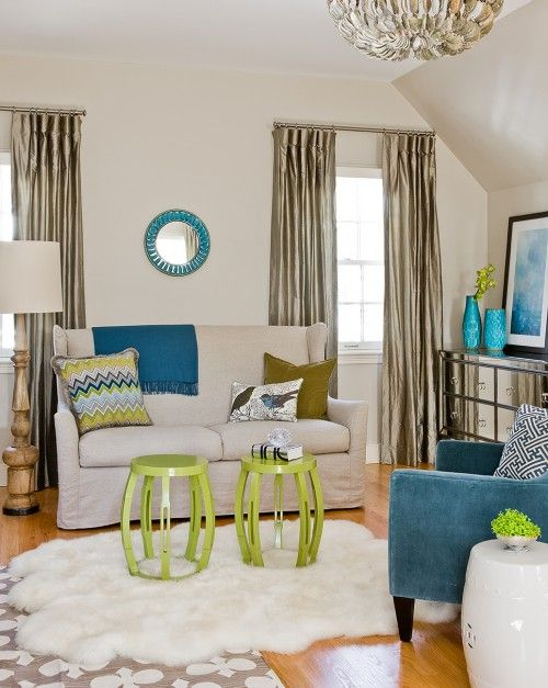 Gorgeous living area in master bedroom with ivory walls paint color, windows covered in taupe silk curtains window panels flanking linen wingback slipcover sofa, turquoise blue round mirror,