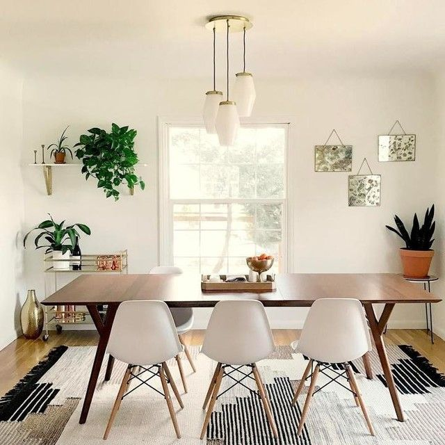 Favorite Dining Room Setup - West Elm Expandable Mid-Century Modern walnut wood dining table, replica Eames white chairs with wooden legs, lots of plants and handwoven Colca Wool Rug $899 - geo-tribal aztec print pattern, earthy tones, neutral palette accented with bronze threading