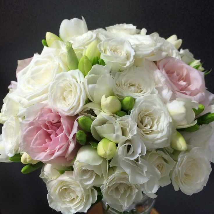 White & some pale pink roses, white spray roses, lisianthus & freesias create this delicate posy