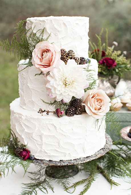 A three-tiered wedding cake decorated with a white dahlia, blush roses, gold-dusted berries, and greenery, created by Elise Cakes.  #weddings #weddingcakes #cakes.
