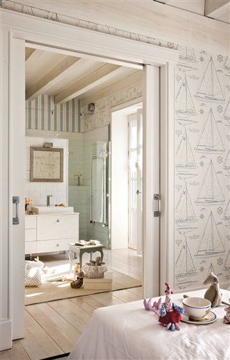 nautical wallpaper, pocket doors, bleached wood, and a view of a contemporary bathBedrooms, Bathroom