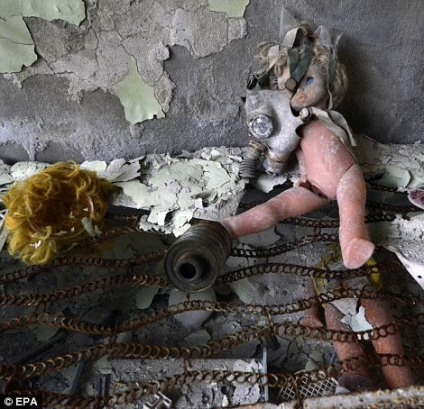 A gas mask lies on a doll in an abandoned building in the deserted town of Pripyat