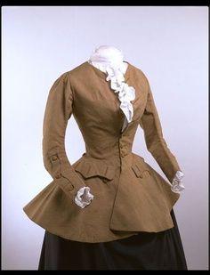 Hábitos de conducción de las mujeres del siglo 18 adaptado elementos de vestido de los hombres. Esta chaqueta de lana marrón cosida a mano de la década de 1750 es de estilo después de un abrigo de hombre, aunque se ha modificado con una costura de la cintura para encajar en estancias y una amplia enagua.