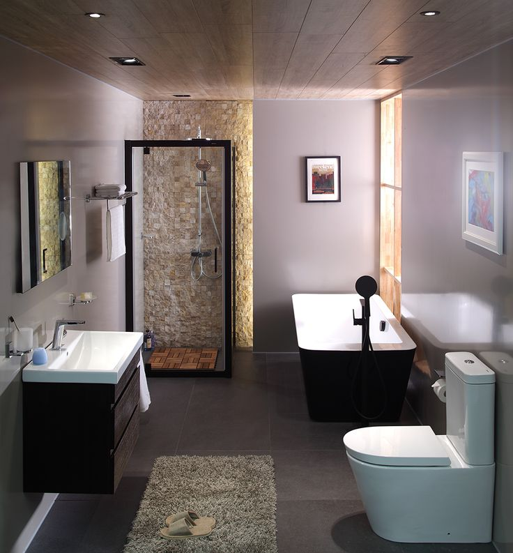 A bathroom with shower screen, bathtub, toilet, and vanity