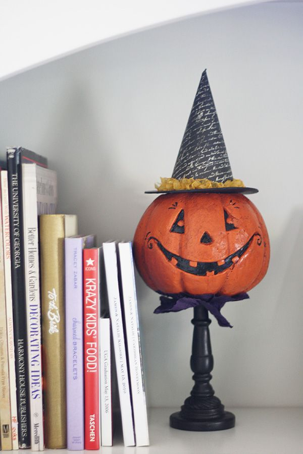 Jack o lantern on a candle stick with a witch hat.