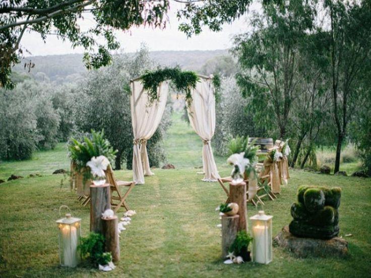 autel de mariage en plein air - voiles blancs, déco de fleurs et branchettes et lanternes